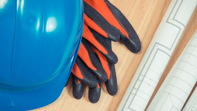 Rolls of diagrams and electrical construction drawings, protective blue helmet and gloves
